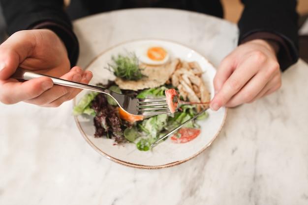 Салат и руки с ножом и вилкой крупным планом, вид сверху. мужчина ест салат в ресторане.