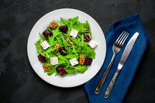 Salad of arugula, cheese, beetroot, walnut, on a background of slate, stone or concrete.