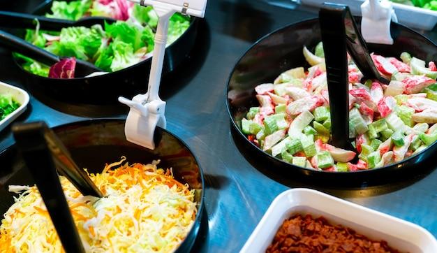 レストランでのサラダバービュッフェ。ランチまたはディナーに新鮮なサラダバービュッフェ。健康食品。セロリとカニカマをカウンターの黒いボウルにスライスしました。ケータリング食品。宴会サービス。ベジタリアンフード。