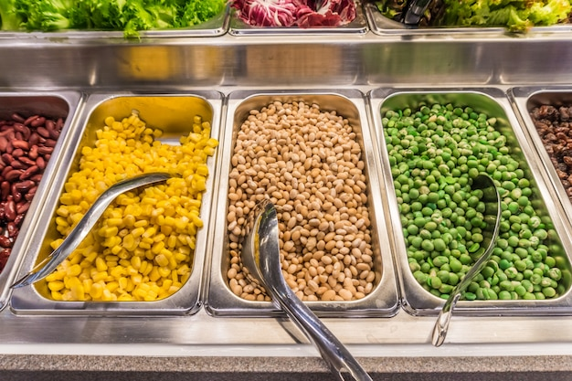 Salad bar with vegetables in silver trays in the restaurant, healthy food. select focus