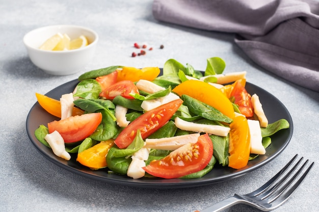 Salad of boiled squid, fresh tomatoes, spinach leaves. delicious bright diet dish with vegetables and seafood.