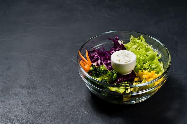 Salad bowl, healthy vegetarian food. ingredients broccoli, corn, carrots, couscous, lettuce, cabbage, sauce.
