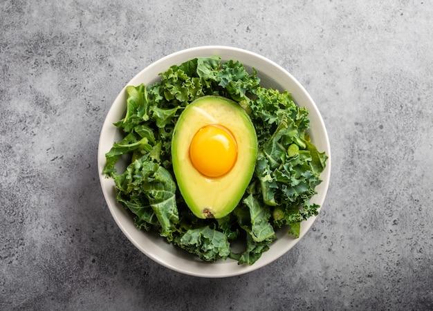 Салатник с капустой для сбалансированного меню, сырой яичный желток в свежей половинке авокадо, богатой полезными жирами, на сером каменном фоне. кетогенная диета с низким содержанием углеводов или концепция чистого питания