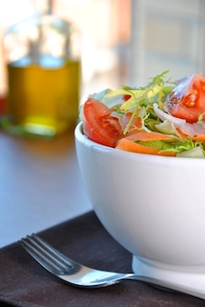 Salad bowl with lettuce, carrot, tomato and onion
