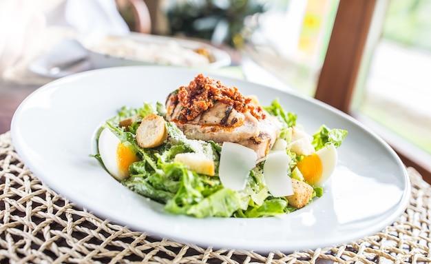 Салат цезарь с жареными кусочками куриной грудки на белой тарелке в ресторане.