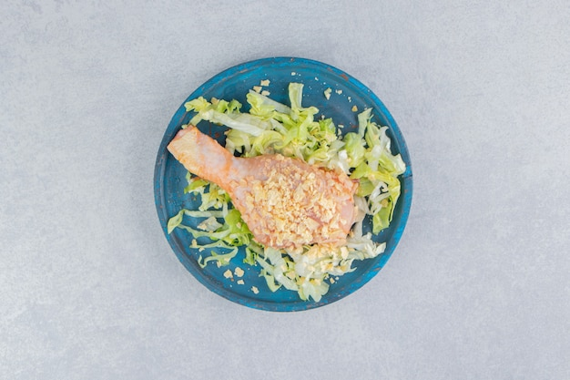 Salad and chicken leg in the wooden plate , on the blue surface