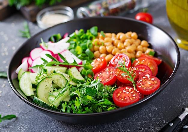 Salad of chickpeas, tomatoes, cucumbers, radish and greens. dietary food. buddha bowl. vegan salad.