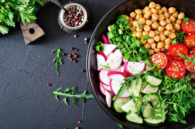 Salad of chickpeas, tomatoes, cucumbers, radish and greens. dietary food. vegan salad. top view. flat lay. buddha bowl