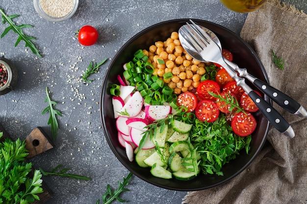 Salad of chickpeas, tomatoes, cucumbers, radish and greens. dietary food. vegan salad. top