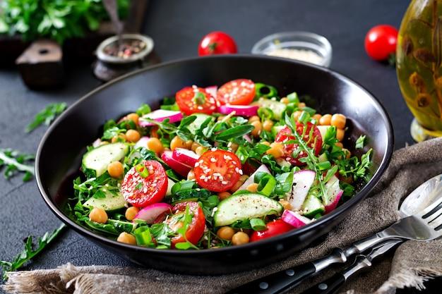 Salad of chickpeas, tomatoes, cucumbers, radish and greens. dietary food. vegan salad.