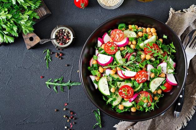 Salad of chickpeas, tomatoes, cucumbers, radish and greens. vegan salad. top view.