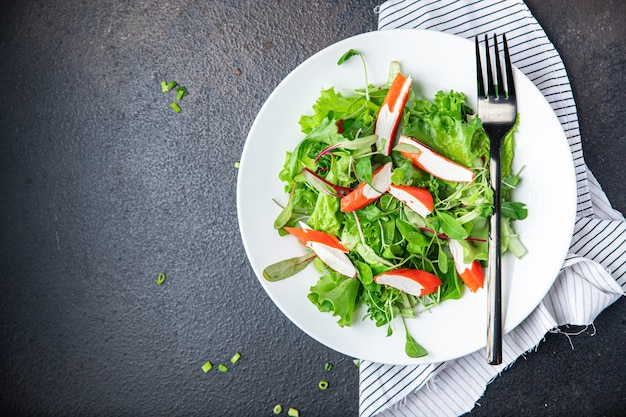 Salad crab stick green lettuce leaves mix petals fresh portion meal snack on the table copy space