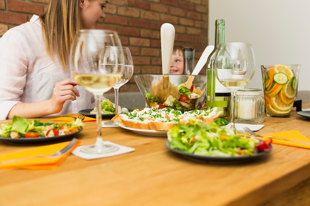 Salad dishes on table and family