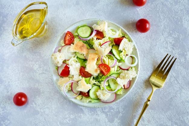 Салат фаттуш. здоровое вегетарианское питание. традиционный ближневосточный салат с поджаренным лавашем и овощами в белой тарелке на светлом фоне. крупным планом, вид сверху.