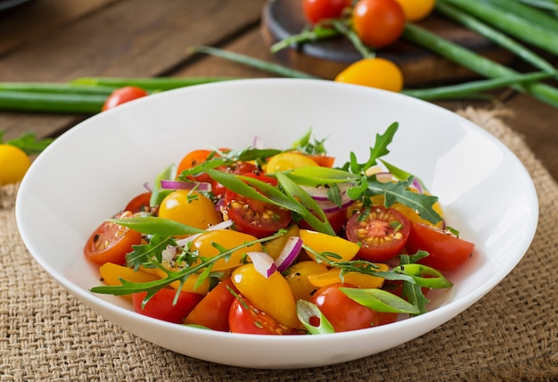 Salad of fresh cherry tomatoes with onion and arugula