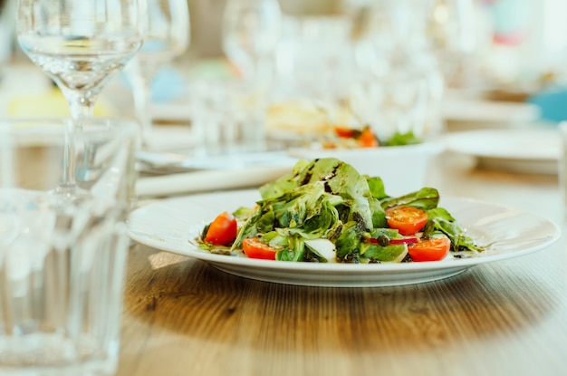 Salad of fresh vegetables and herbs with pesto on the table in the restaurant