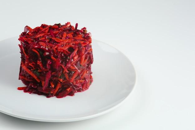 신선한 야채 양배추, 사탕무, 당근 샐러드. 고립 된 하얀 접시에 양배추와 비트 샐러드