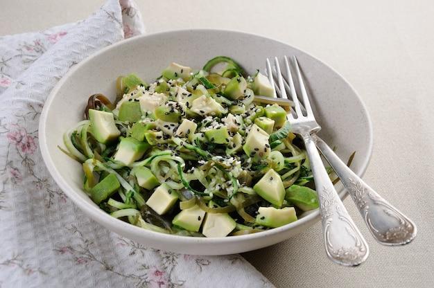 Салат из лапши из огурцов и ламинарии, ломтики авокадо с кунжутом