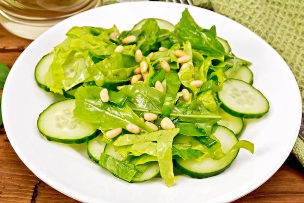 ほうれん草のサラダ、新鮮なキュウリ、ルッコラサラダ、杉の実、ネギ、皿に植物油で味付け、木の板の背景にナプキンとフォーク