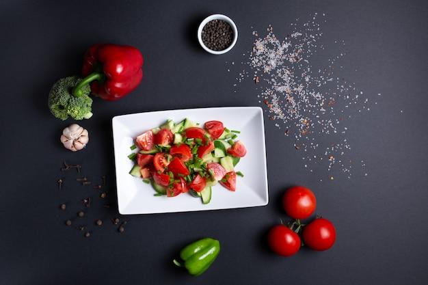 Салат из помидоров и огурцов, на черном с помидорами, чесноком, красным зеленым перцем и брокколи