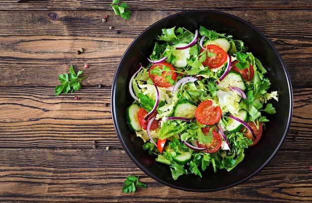 Салат из помидоров, огурцов, красного лука и листьев салата. здоровое летнее витаминное меню. веганская овощная еда. вегетарианский обеденный стол. вид сверху. плоская планировка