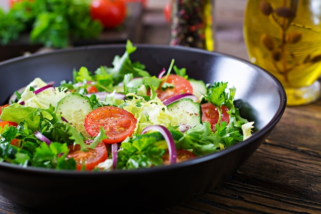 Salad from tomatoes, cucumber, red onions and lettuce leaves. healthy summer vitamin menu. vegan vegetable food. vegetarian dinner table.