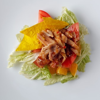 Salad from vegetables and meat on a white background.
