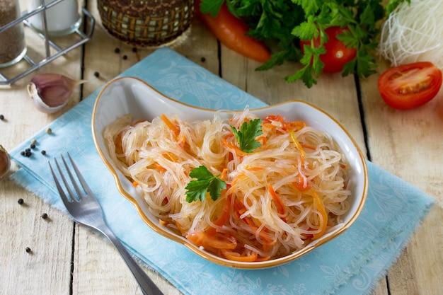キッチンの木製テーブルにパプリカトマトと唐辛子を添えたライスヌードルのサラダフンチョザ中華料理焼きそば