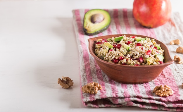 Salad of germinated buckwheat, avocado, walnut and pomegranate seeds in clay plate on white wooden background.