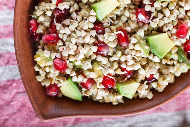 Salad of germinated buckwheat, avocado, walnut and pomegranate seeds in clay plate