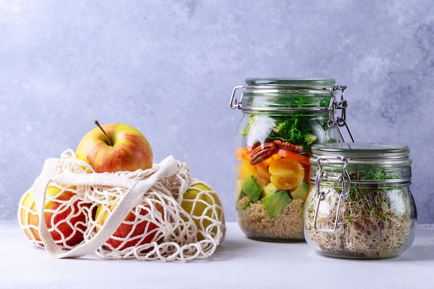 Salad in glass jar and mesh bag with apples eco-shopping concept
