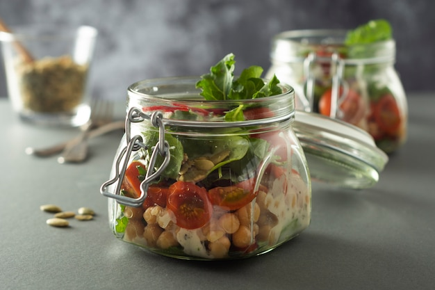 Salad in glass jar with fresh vegetables and chick pea. healthy food, diet, detox.