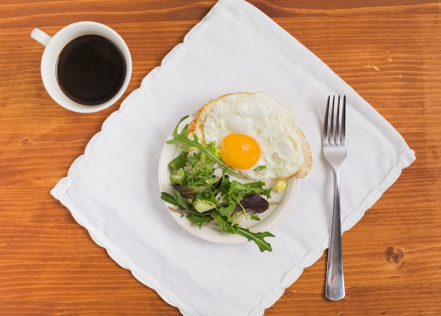 Salad and half fried egg on plate over the napkin with cup of tea