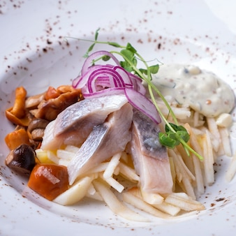 Salad  herring, apple and mushrooms on a plate, closeup