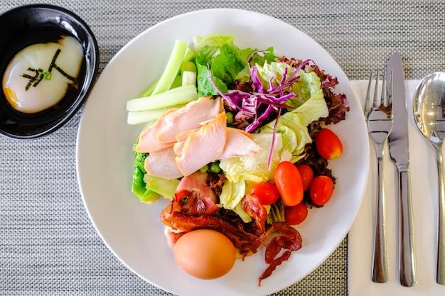 Салат хот-дог суши в белой тарелке и ложка с кифом на столе