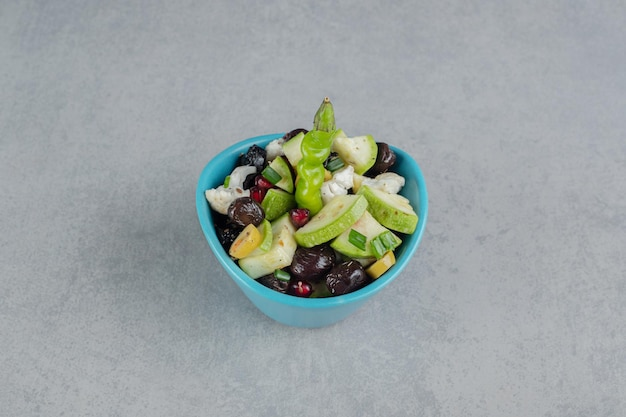 みじん切りの野菜と果物を混ぜた青いカップのサラダ。