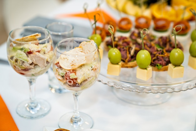 グラスとカナッペのサラダビュッフェテーブルの快適なサービング