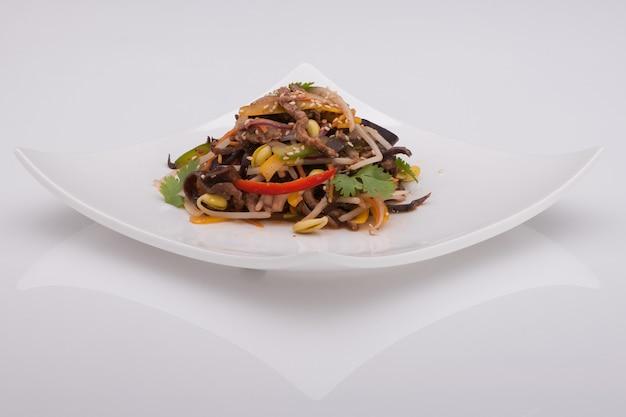 Салат в белой тарелке на белом фоне