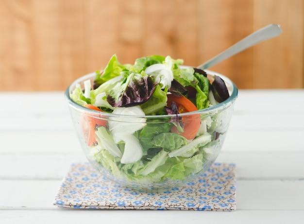 白い木製のガラスのボウルのサラダ