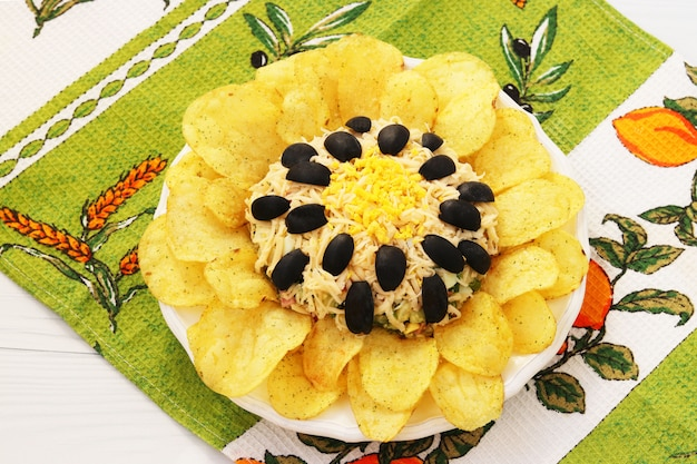 プレートにあるポテトチップスで飾られたヒマワリの形のサラダ