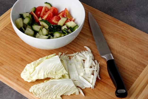サラダの材料。トマトとキュウリのみじん切りのボウルと、暗いテーブルの上に白菜のみじん切りとナイフが付いたまな板。