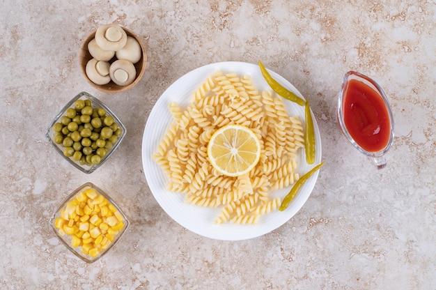 Ингредиенты салата рядом с основным блюдом на мраморной поверхности