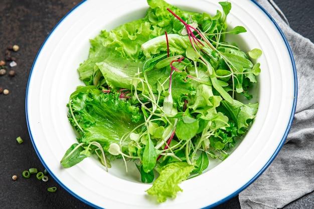 サラダの葉は新鮮なハーブの花びらを混ぜ合わせますテーブルの上で食事の軽食を食べる準備ができている新鮮なビタミン食前酒