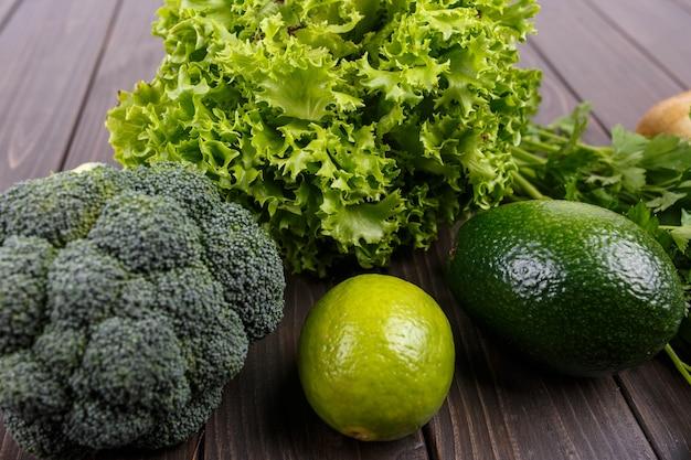 Salad, lime, broccoli, parsley and avocado lie on the table