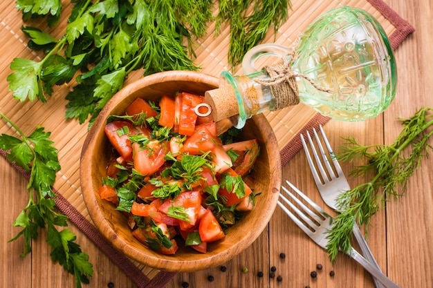 Salad made of tomatoes and fresh herbs,  oil and fork on wooden table. top view