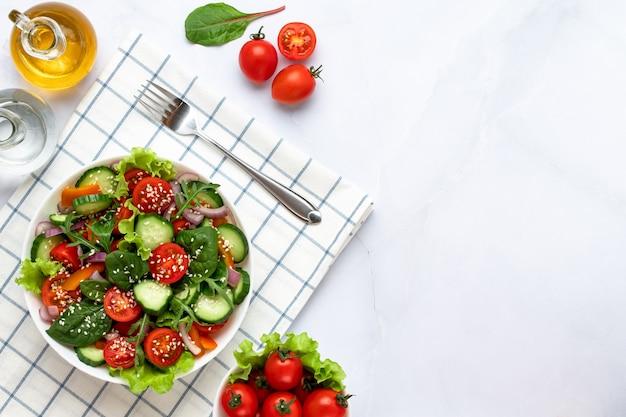 Салат из кусочков помидоров, огурцов, лука, ломтиков болгарского перца, рукколы, кунжута, базилика и заправленный оливковым маслом. концепция здорового питания, вегетарианская диета. скопируйте пространство, пустое место для текста.