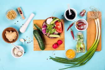 Salad making. Cutlery and dressing ingredients for fresh salad on light blue background, top view