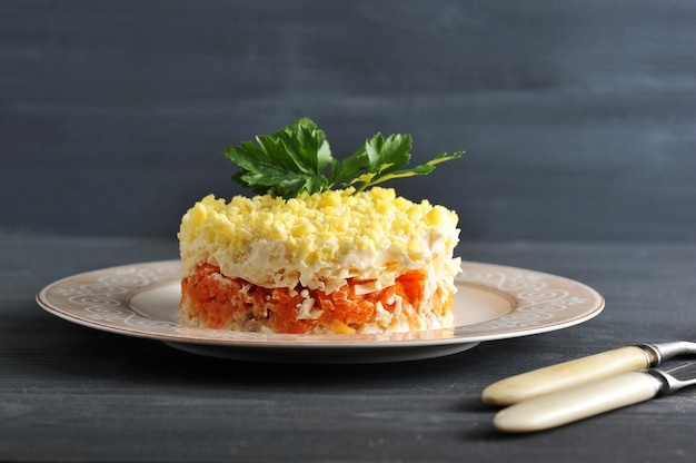 Salad mimosa with fish, carrots and eggs