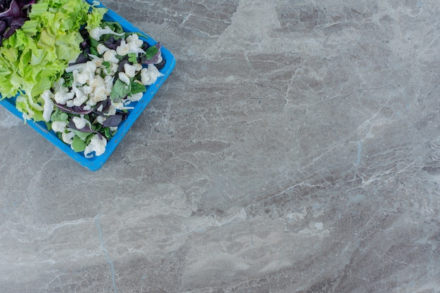 Salad mix of cauliflower, cabbage and amaranth on a blue platter on marble.
