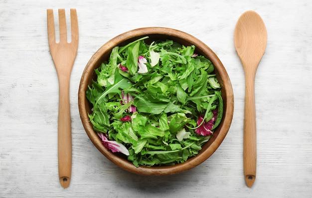 Смесь салата в миске на деревянном столе